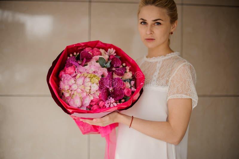 Flickan rymmer buketten av olika rosa blommor arkivfoto