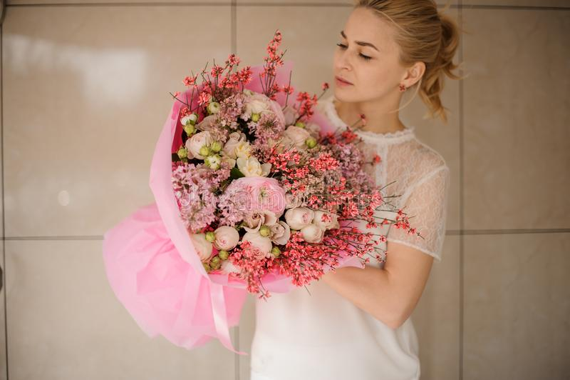 Flickan rymmer den rosa buketten av olika blommor arkivbilder