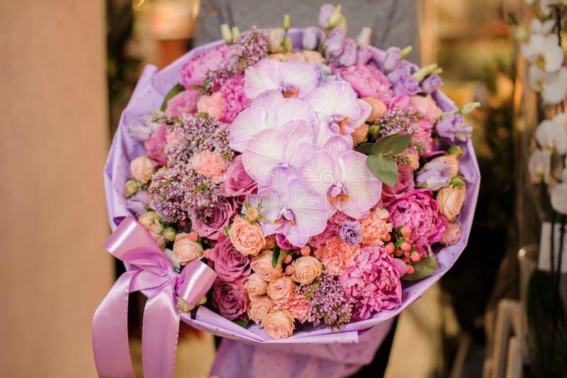 Flickan rymmer en bukett av olika rosa färger och purpurfärgade blommor, inklusive orkidér royaltyfri foto