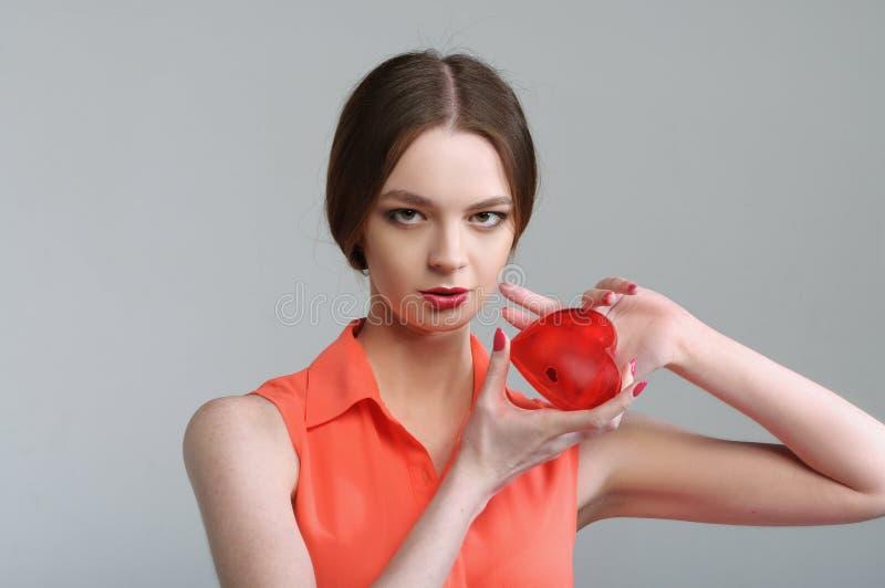 Flickan rymmer en inverterad röd hjärta nära hennes bröst royaltyfria foton