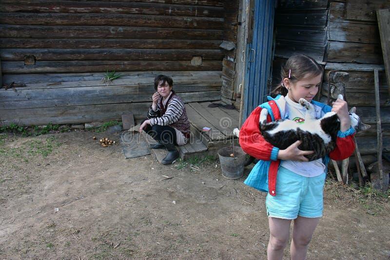 Flickan rymmer en katt, nära lantbrukarhemmet, bygd, Ryssland royaltyfri fotografi