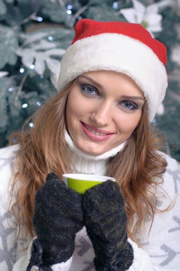 Flickan rymmer en kopp te eller ett kaffe arkivfoto
