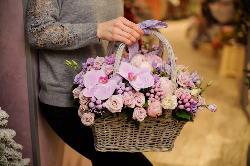 Flickan rymmer en korg av purpurfärgade blommor inklusive rosor och orkidér royaltyfria foton