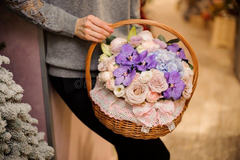 Flickan rymmer en korg med purpurfärgade orkidér, rosa rosor och den blåa vanliga hortensian arkivbilder