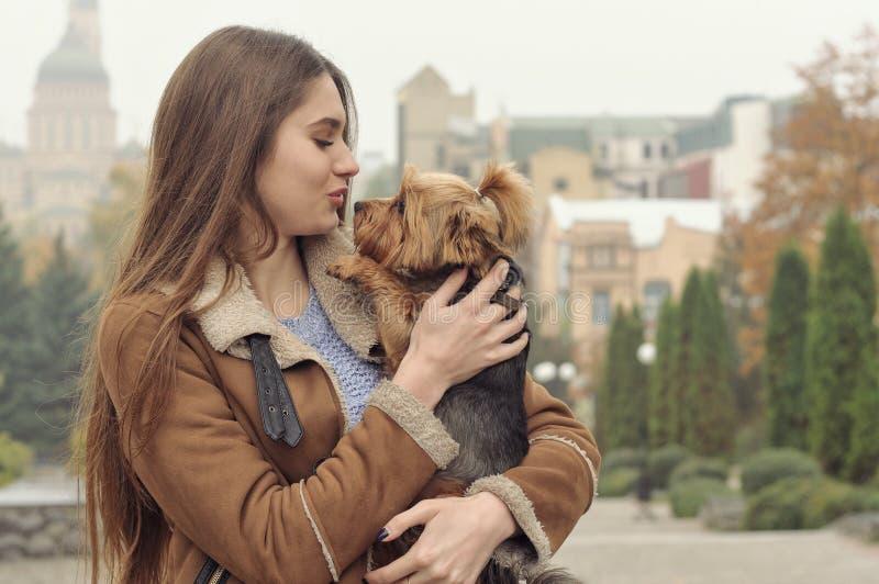 Flickan rymmer en liten hund i hennes armar, kramar och kysser henne arkivfoton