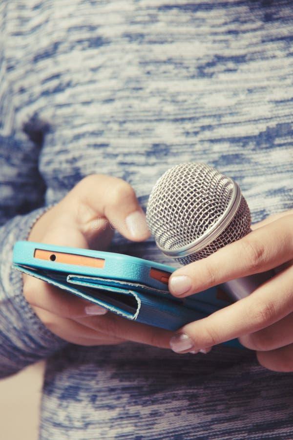 Flickan rymmer en mikrofon i hennes hand och söker efter en sång i telefonen för karaokekapacitet arkivbilder