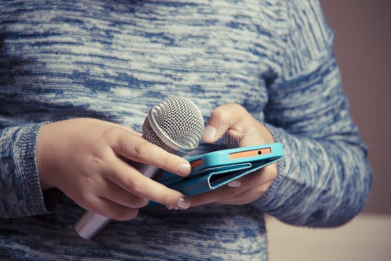 Flickan rymmer en mikrofon i hennes hand och söker efter en sång i telefonen för karaokekapacitet royaltyfria foton