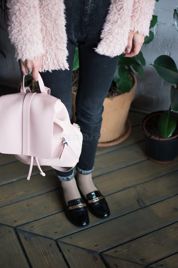 Flickan rymmer en rosa ryggsäck i skor med en skarp näsa royaltyfri bild