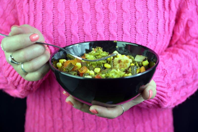Flickan rymmer en svart platta med grönsaker i hennes händer royaltyfri fotografi