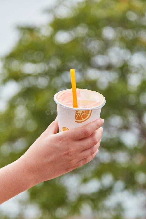 Flickan rymmer ett exponeringsglas av orange fruktsaft royaltyfria bilder