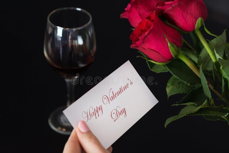 Flickan rymmer ett pappers- kort med en lycklig valentindag för meddelande i hennes hand och röda ros- och vinexponeringsglas på  royaltyfri bild