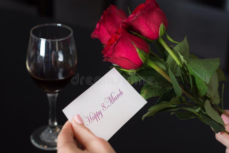 Flickan rymmer ett pappers- kort med ett meddelande lyckliga 8 Mars i hennes hand och röda ros- och vinexponeringsglas på den sva royaltyfria foton