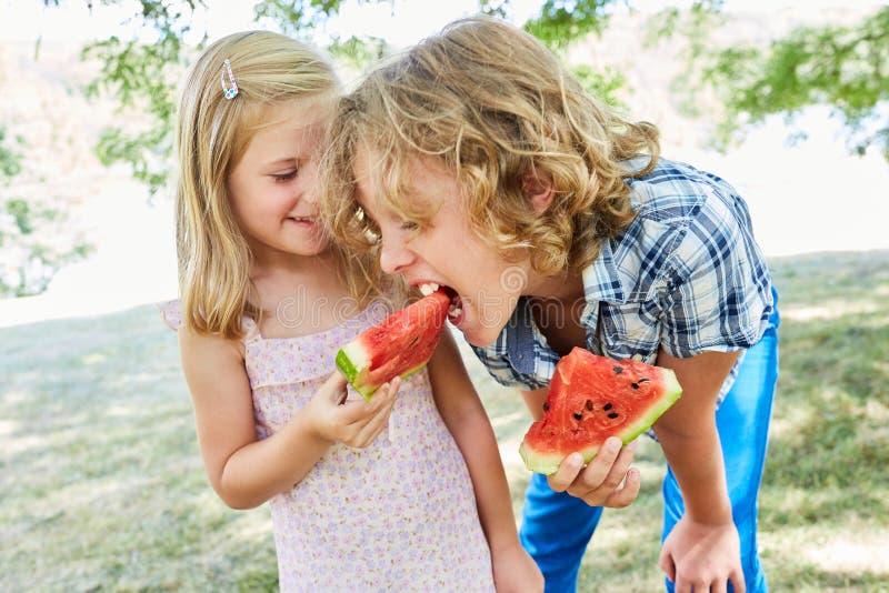 Flickan rymmer ett sött stycke av melon royaltyfri fotografi