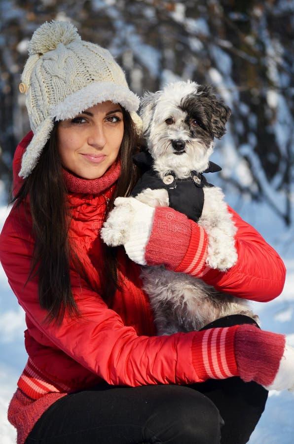 Flickan rymmer henne little klädd hund royaltyfri bild