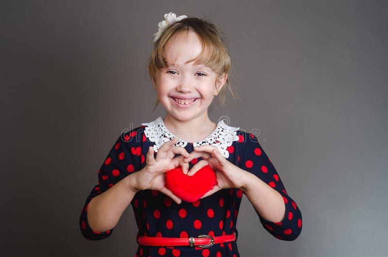 Flickan rymmer hjärta i hand och ler arkivbild