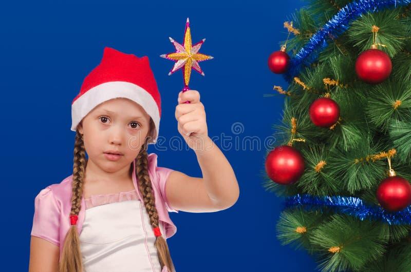 Flickan rymmer i hand en stjärna på ett grönt gran-träd arkivfoto