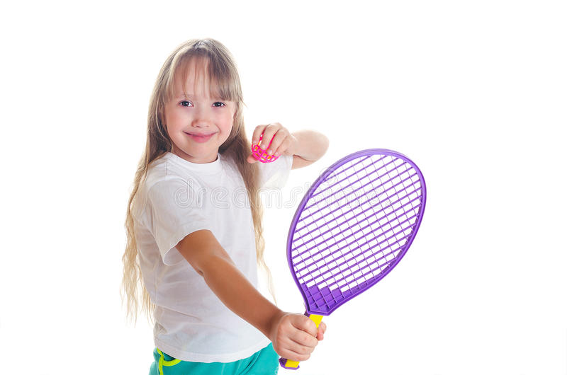 Flickan rymmer i hand en tennisracket med en boll och ler fotografering för bildbyråer