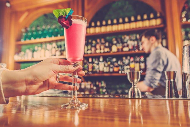 Flickan rymmer i hans hand per exponeringsglas av alkoholdrycken arkivfoto
