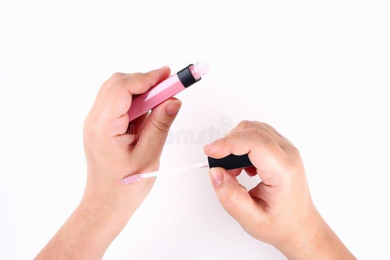Flickan rymmer i hennes hand en rosa kantglans på vit bakgrund Top besk?dar arkivfoton