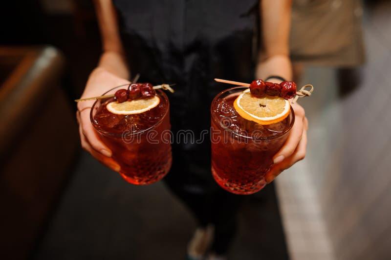 Flickan rymmer nergoni för två alkoholiserad coctailar med citronen och körsbäret royaltyfria bilder