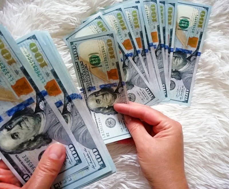 Flickan rymmer pengarna i hennes händer Hundra dollar kassa arkivbilder