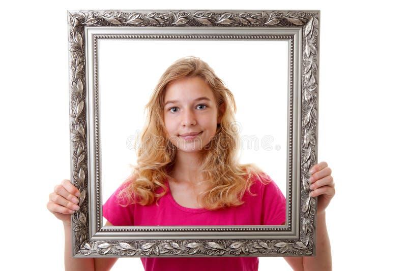 Flickan rymmer ramen royaltyfria foton