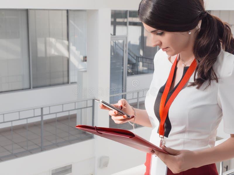 Flickan rymmer telefonen i henne händer Härlig le bakgrund för affärskvinnaStanding Against White kontor Stående av royaltyfria bilder