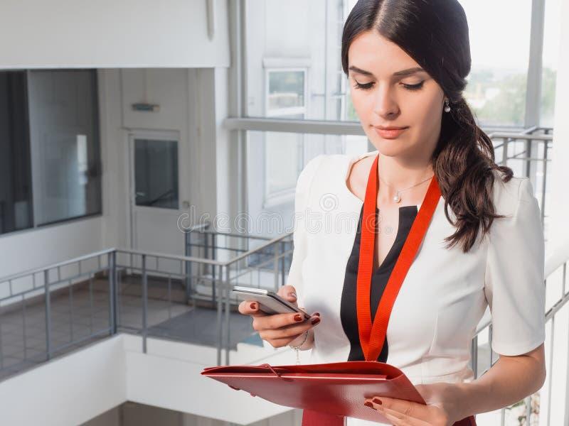 Flickan rymmer telefonen i henne händer Härlig le bakgrund för affärskvinnaStanding Against White kontor Stående av arkivfoto
