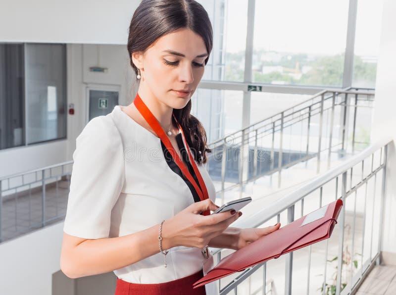 Flickan rymmer telefonen i henne händer Härlig le bakgrund för affärskvinnaStanding Against White kontor Stående av royaltyfri bild