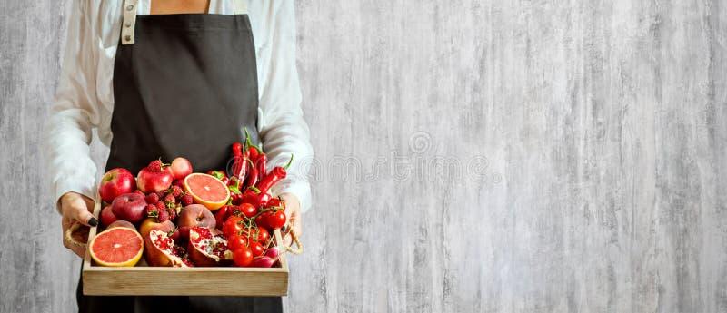 Flickan rymmer trämagasinet med nya röda grönsaker och frukter på grå bakgrund Sunt vegetariskt begrepp för äta royaltyfri fotografi