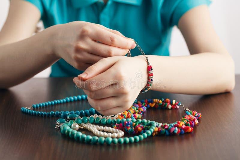 Flickan sätter armbandet på hans hand och en grupp av smycken royaltyfri fotografi