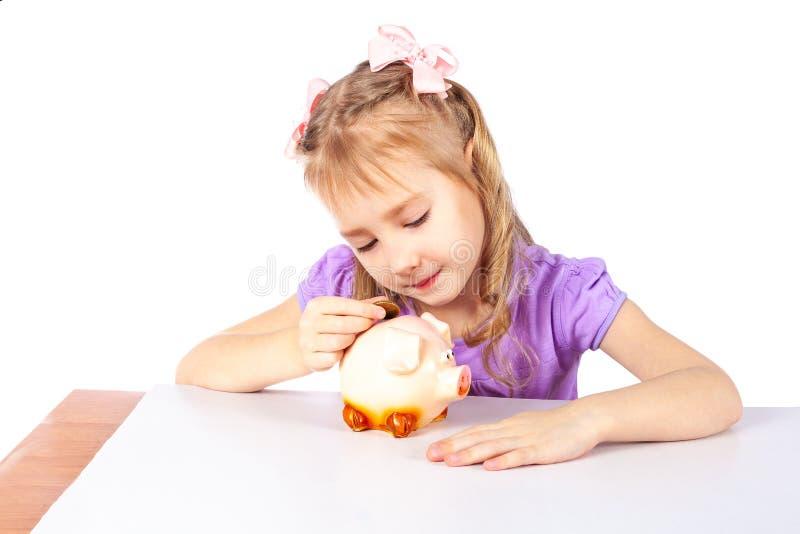 Flickan sätter ett mynt i en spargris royaltyfri bild