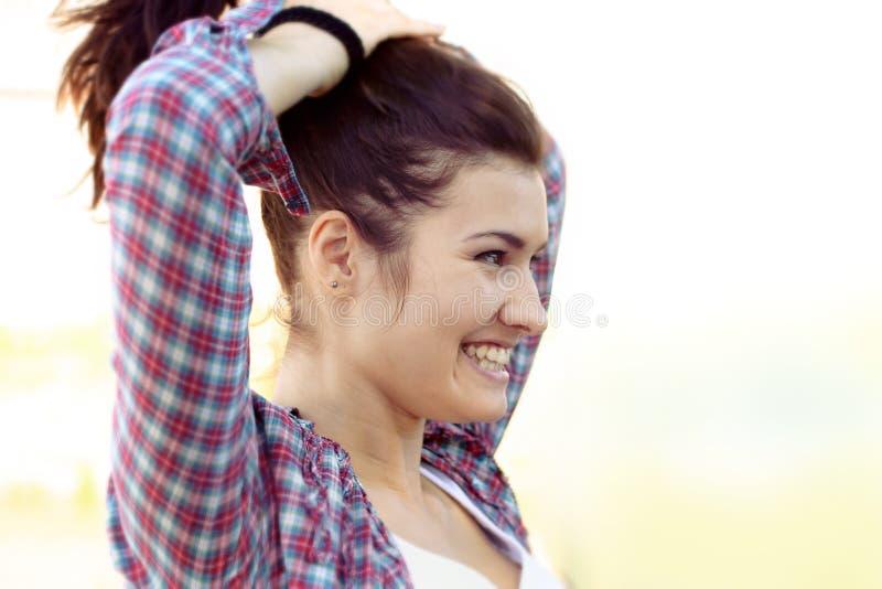 Flickan sätter hennes hår och glatt skratt royaltyfri fotografi