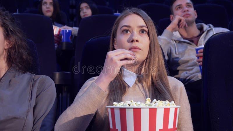 Flickan sätter långsamt popcornet i hennes mun på filmbiografen arkivfoton