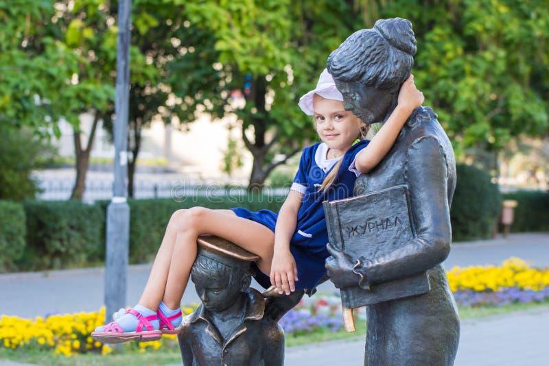 Flickan satt bekvämt på monumentet till den första läraren royaltyfri fotografi