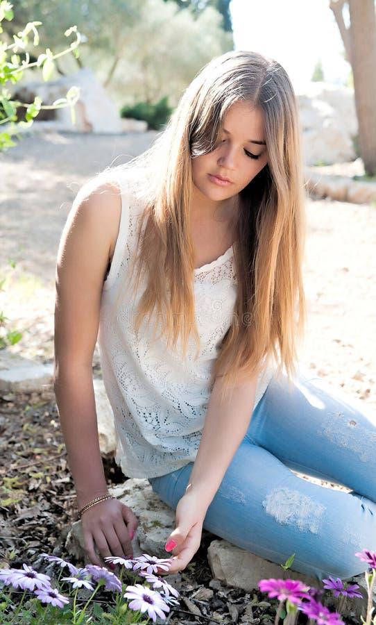 Flickan satt ner nära blomman arkivbilder
