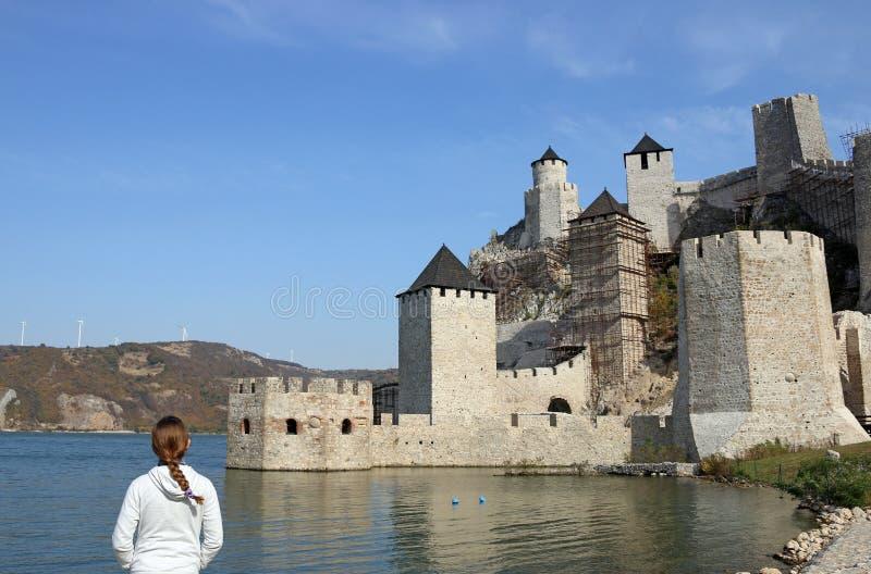 Flickan ser den Golubac fästningen royaltyfri foto