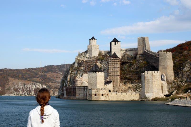 Flickan ser den Golubac fästningen på Danube River fotografering för bildbyråer