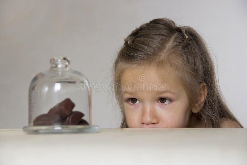 Flickan ser ledsen på sötsakerna under det glass locket arkivbilder