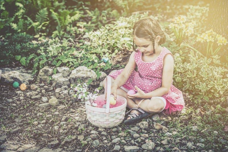 Flickan ser påskägg i hennes Retro korg - royaltyfria foton