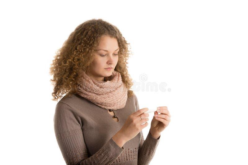 Flickan ser termometern royaltyfria bilder
