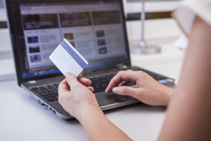 Flickan shoppar på internet I händerna av en plast- kreditkort En kvinna framme av en datorbildskärm på rengöringsduken arkivfoton