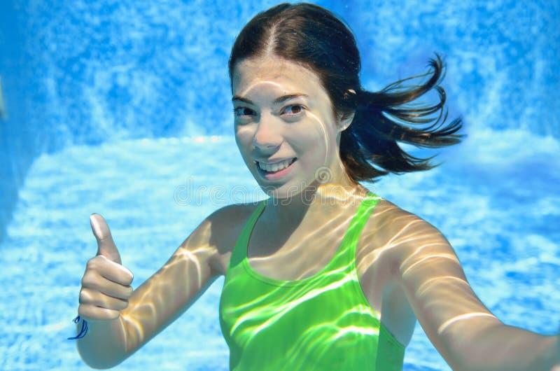 Flickan simmar i den undervattens- simbassängen, den lyckliga aktiva tonåringen dyker och har gyckel under vatten, ungekondition  arkivfoto