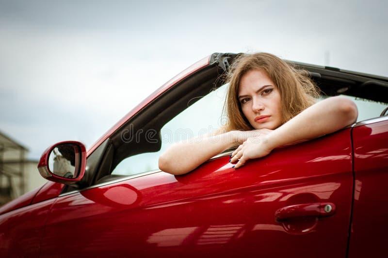 Flickan sitter bak hjulet av en röd bil royaltyfria foton