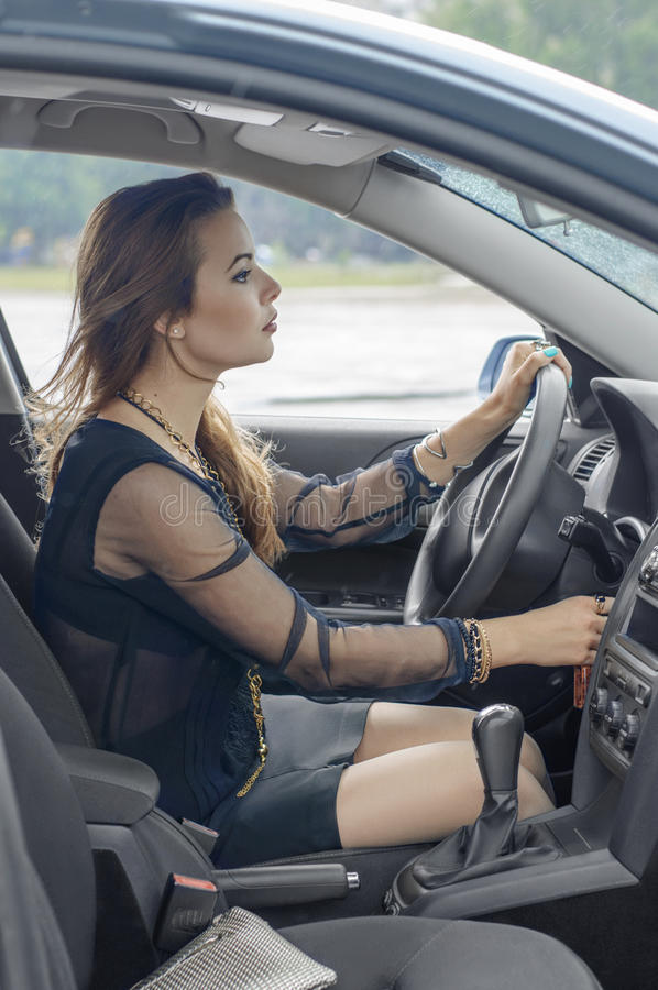 Flickan sitter i en bil som en chaufför fotografering för bildbyråer