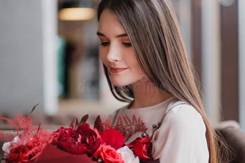 Flickan sitter i ett kafé med en bukett av röda blommor, pioner, rosor och krysantemum arkivbild