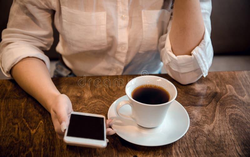 Flickan sitter i ett kafé och rymmer en kopp te och en telefon i hennes händer som väntar på en appell arkivbild