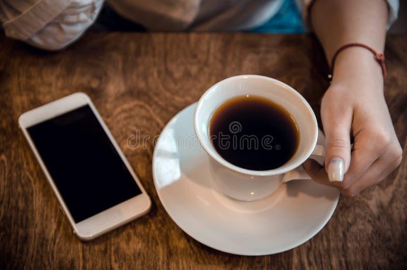 Flickan sitter i ett kaf? och rymmer en kopp te och en telefon i hennes h?nder som v?ntar p? en appell arkivfoto
