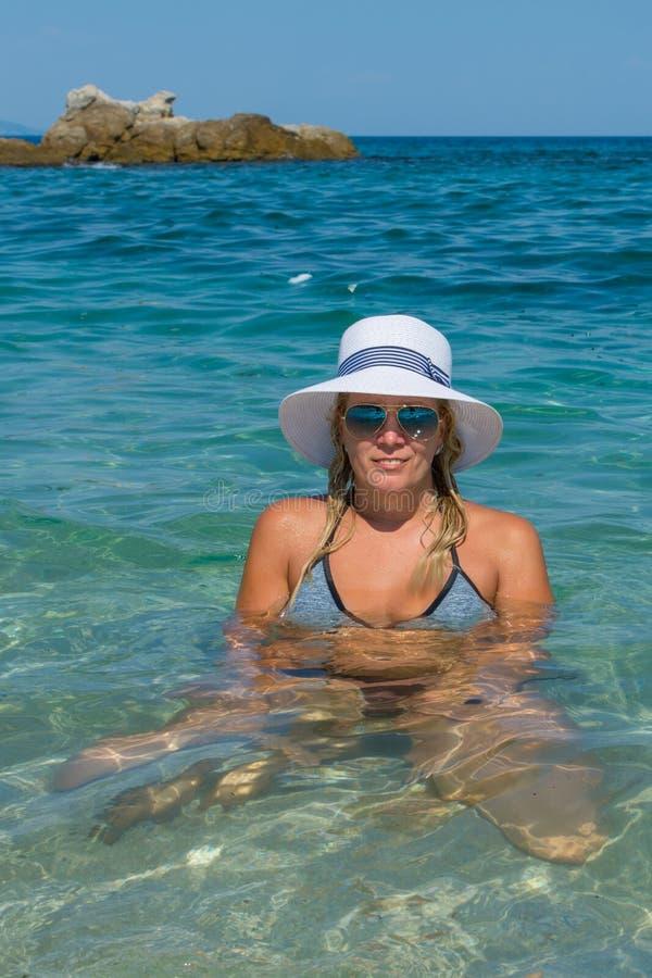 Flickan sitter i havet med en hatt och solglasögon arkivbild