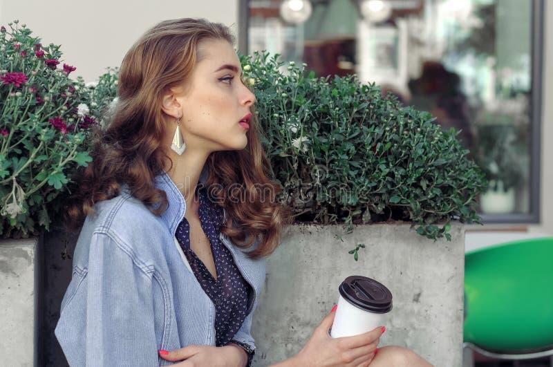 Flickan sitter med pappers- koppar för drinkar fotografering för bildbyråer